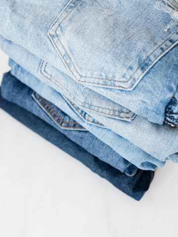 stack of jeans on white marble surface