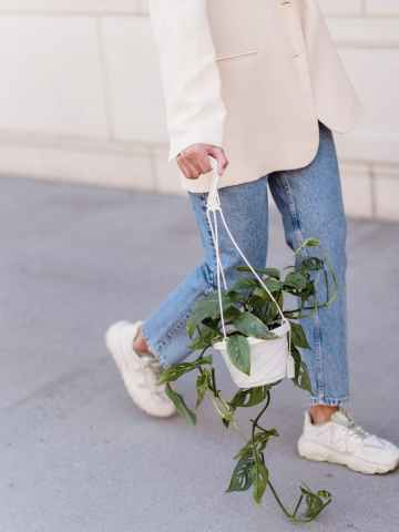 unrecognizable woman with hanging flowerpot