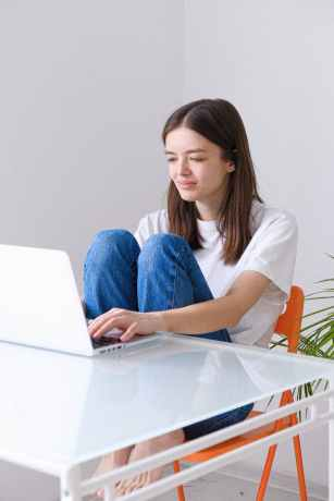 woman in white shirt and blue denim jeans sitting on chair using laptop