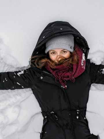 woman in black jacket and gray knit cap on snow covered ground